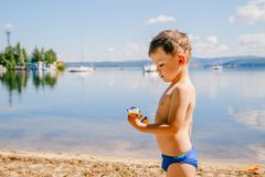 Tanned boy of three years in swimming trunks plays on the lake in the summer, summer vacation, childhood. Lake stock images