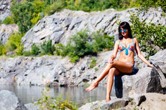 Tanned brunette girl in a colorful bikini sits on a rock near a Royalty Free Stock Images