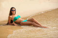 Tanned brunette laying on the beach Royalty Free Stock Images