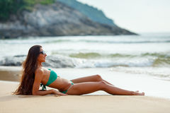 Tanned brunette laying on the beach Stock Images