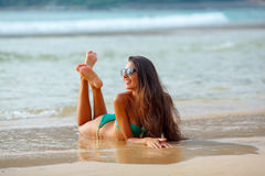 Tanned brunette laying on the beach Royalty Free Stock Image
