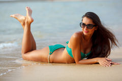 Tanned brunette laying on the beach Stock Image