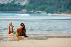 Tanned brunette laying on the beach Royalty Free Stock Photos