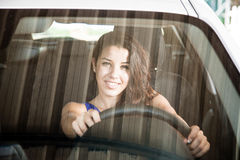 Tanned brunette looking through car windscreen smiling Stock Image