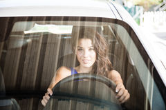 Tanned brunette looking through car windscreen smiling Royalty Free Stock Image