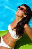Tanned brunette in pool Royalty Free Stock Image