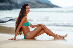 Tanned brunette sitting on the beach Stock Photography