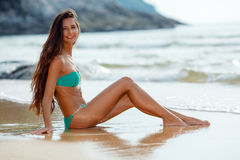 Tanned brunette sitting on the beach Stock Photos