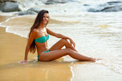 Tanned brunette sitting on the beach Stock Images