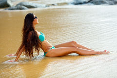 Tanned brunette sitting on the beach Royalty Free Stock Photo
