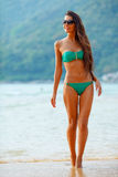 Tanned brunette walking along the beach Royalty Free Stock Photos