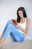 Tanned casual young woman relaxing with a tablet Royalty Free Stock Images