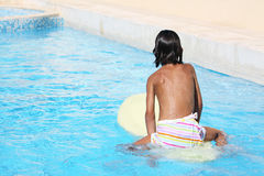 Tanned child on a surfboard. Tanned caucasian child on a surfboard in a swimming pool Stock Photography