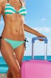Tanned deu forma ao corpo da praia com mala de viagem cor-de-rosa fotos de stock
