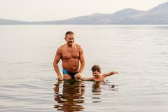 Tanned father and son in swimming trunks stand in the lake, holding hands stock photography