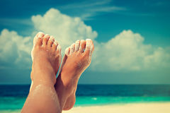 Tanned feet with pedicure. With white Sands and the turquoise sea and blue sky Royalty Free Stock Photo