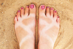 Tanned feet on the sandy beach Stock Image