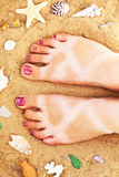 Tanned feet on the sandy beach Royalty Free Stock Photography