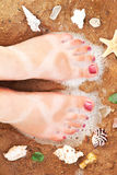 Tanned feet on the sandy beach Royalty Free Stock Photos