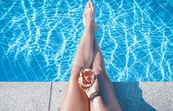 Tanned female legs against the background of the pool with blue. Water Royalty Free Stock Image