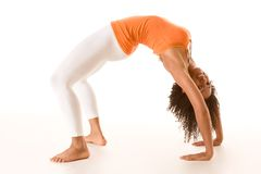 Tanned female in sport clothes performing bridge. Dark skinned fit woman holding bridge stretching pose Stock Images