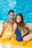 Tanned fit couple relaxing at a sunny pool. royalty free stock photography