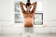 Tanned fit woman stretching hands behind your back in sunny sport gym royalty free stock image