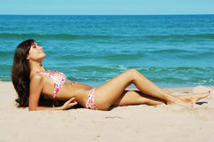 Tanned girl on the beach Stock Photography