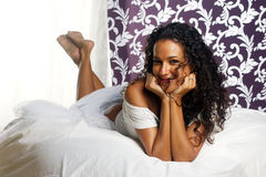 Tanned girl on bed - head in hands Stock Image