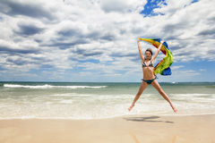 Tanned girl in bikini jumping on the beach with a colored scarf Royalty Free Stock Image