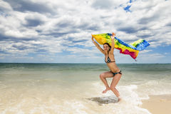Tanned girl in bikini jumping on the beach with a colored scarf Royalty Free Stock Photo