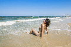 Tanned girl in bikini luxuriating in the waves on the beach Stock Images