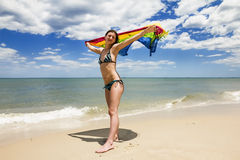 Tanned girl in bikini posing on the beach with colored pareos Royalty Free Stock Images