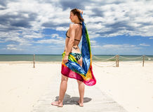 Tanned girl in bikini posing on the beach with colored pareos Stock Photo