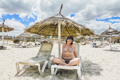 Tanned girl in bikini sitting under an umbrella on the beach Stock Photo
