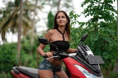 Tanned Girl Caucasian Nationality Driving A Red Otorcycle .journey On A Scooter Stock Photography