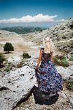 Tanned girl in front of panorama of highland countryside and beautiful nature. Rocky stones and mountains landscape royalty free stock photo