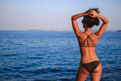 Tanned girl looking at horizon and lifting hair up. Enjoying the sun Stock Photo