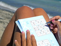 Tanned girl playing sudoku on the seashore Royalty Free Stock Images