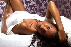Tanned girl smiling across bed Stock Photo