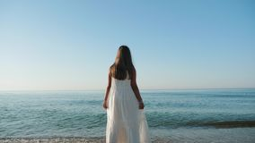 Tanned girl in a white dress looks at the ocean