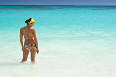 Tanned girls is standing in bright blue ocean Stock Image