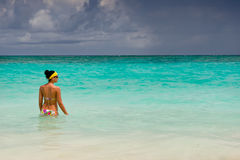 Tanned girls is standing in bright blue ocean Stock Photo