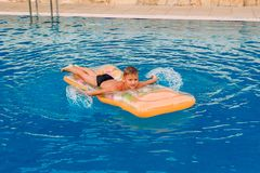Tanned and happy boy floating on an inflatable mattress in an outdoor pool royalty free stock images
