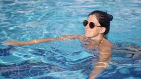 Tanned happy woman in sunglasses relaxing floating at swimming pool enjoying summer vacation
