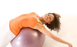 Tanned healthy woman stretching on ball, fitness. Dark skinned female stretching on exercise ball Royalty Free Stock Images