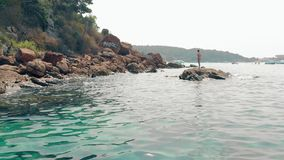 Tanned lady with long hair in red swimsuit stands on stone. Slim tanned lady with long dark hair in bright red bikini stands on big stone among water against stock footage