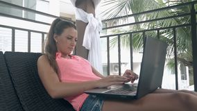 Tanned lady sits in pavilion and surfs internet close view. Serious young tanned lady with long dark ponytail sits in pavilion and surfs internet close view stock video footage