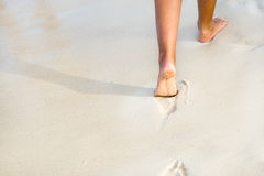 Tanned legs on the beach Royalty Free Stock Images