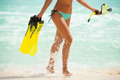 Tanned legs of girl with fins and mask near sea Stock Photos